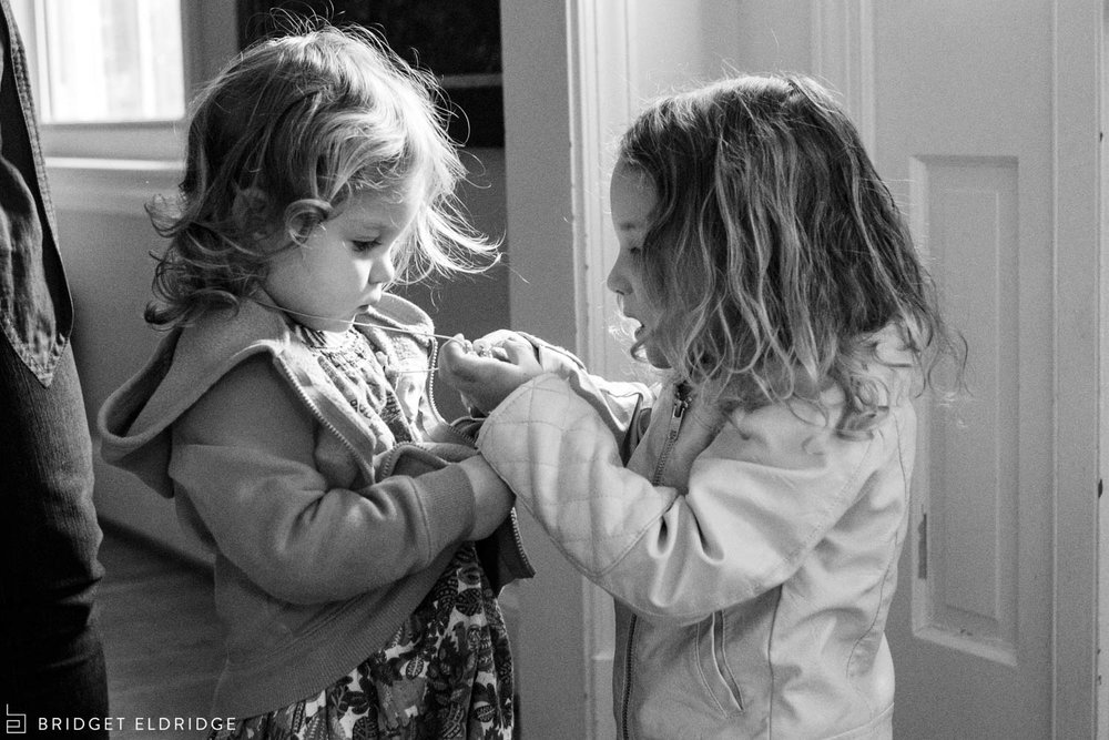 big sister gets her little sister ready to play outside