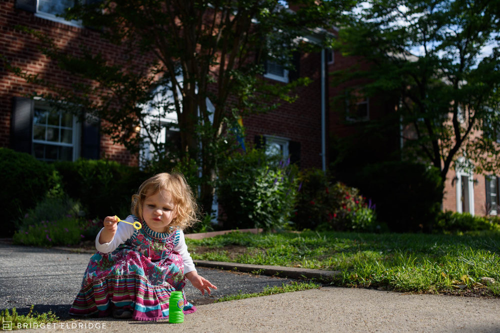 girl blows bubbles outside in her Washington DC neighborhood
