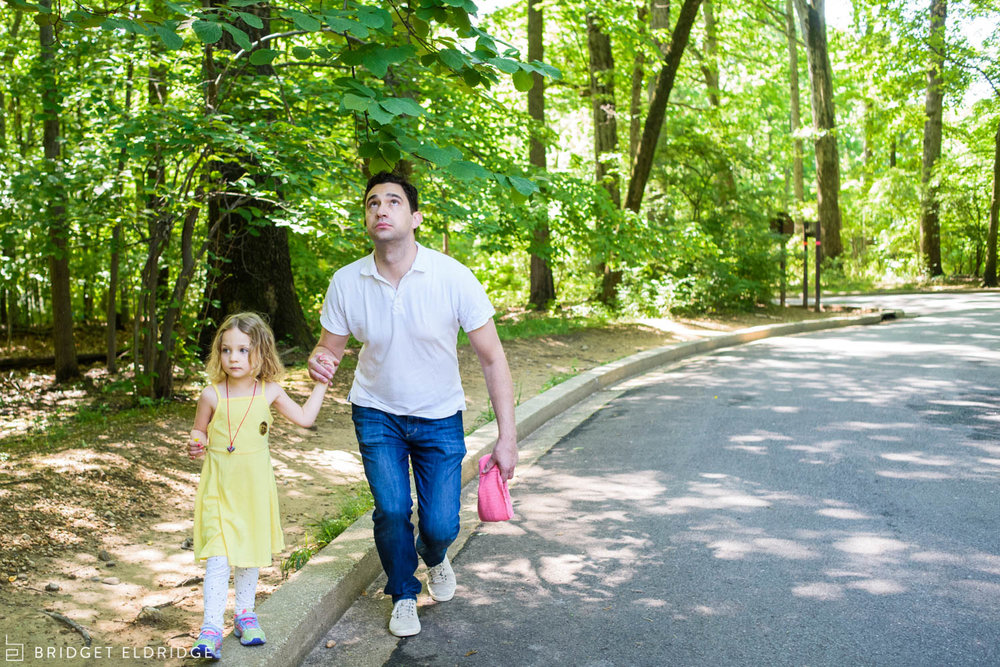 dad ducks under tree branches as he walks his daughter to the car