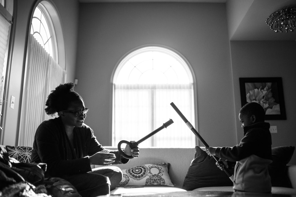 boy and his aunt play light sabers with vacuum clear parts