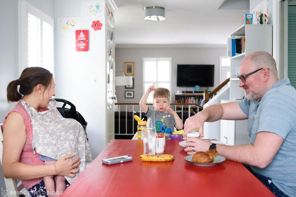 family eats breakfast as mom nurses newborn daughter