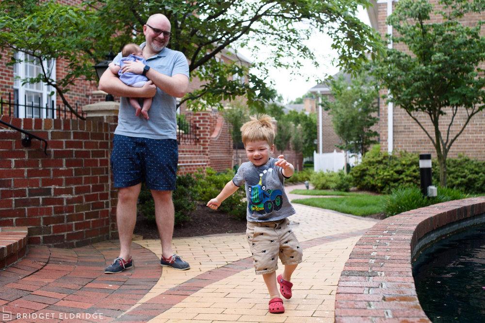 father laughs as son runs away