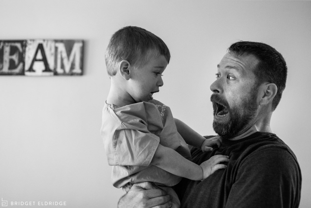 father and son make silly faces at each other
