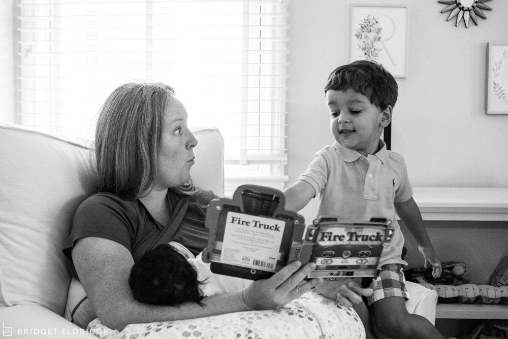 mother reads a book to her son as she nurses her newborn daughter