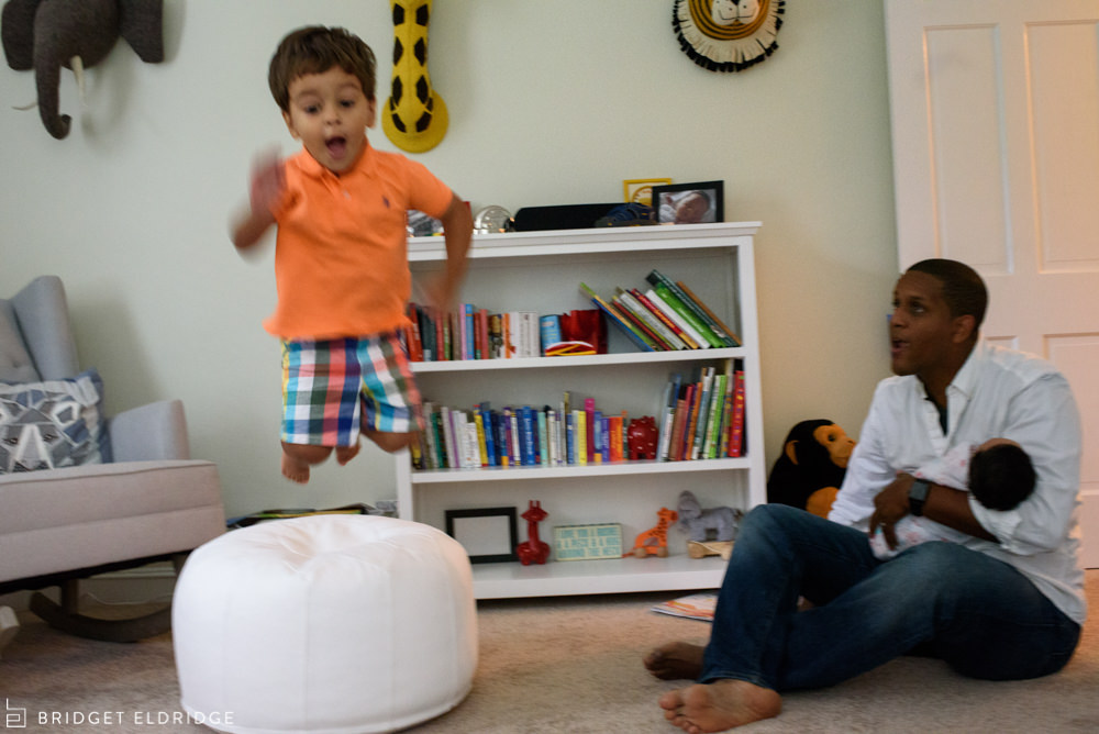 father holds the new baby as his son jumps off an ottoman