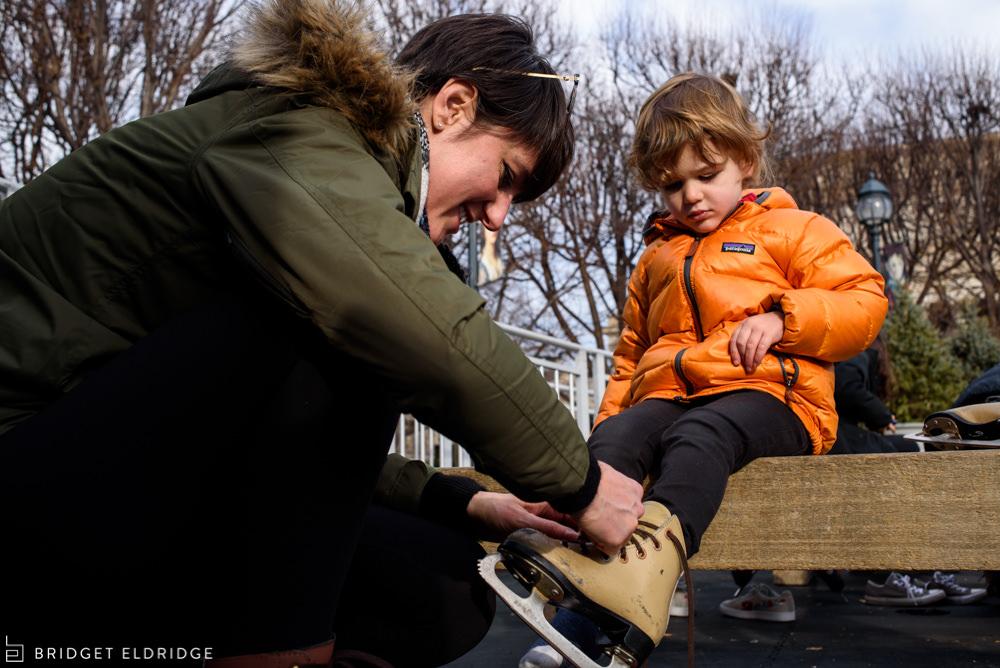 mom ties her son's skates