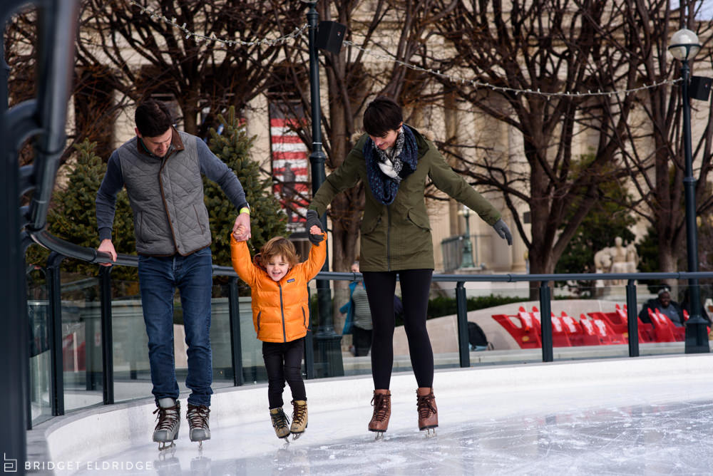 parents hold up three year old as he skates for the first time at the sculpture garden ice rink on the national mall