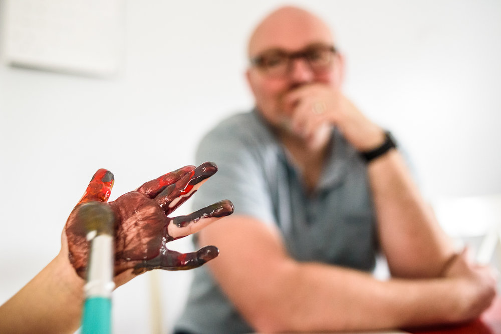 boy paints hand as dad looks on
