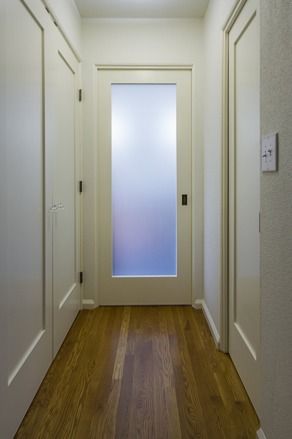 The Master Bathroom is concealed behind a frosted glass pocket door.  Light from a Solatube inside the Bathroom illuminates the glass from  behind.