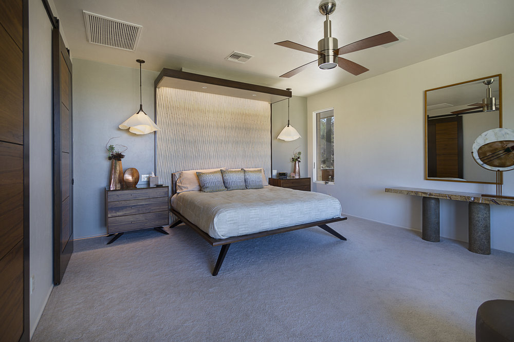 Island Stone tile creates a textured headboard for the bed. The canopy  above, edged in matching rift-sawn white oak, provides a sense of  enclosure.
