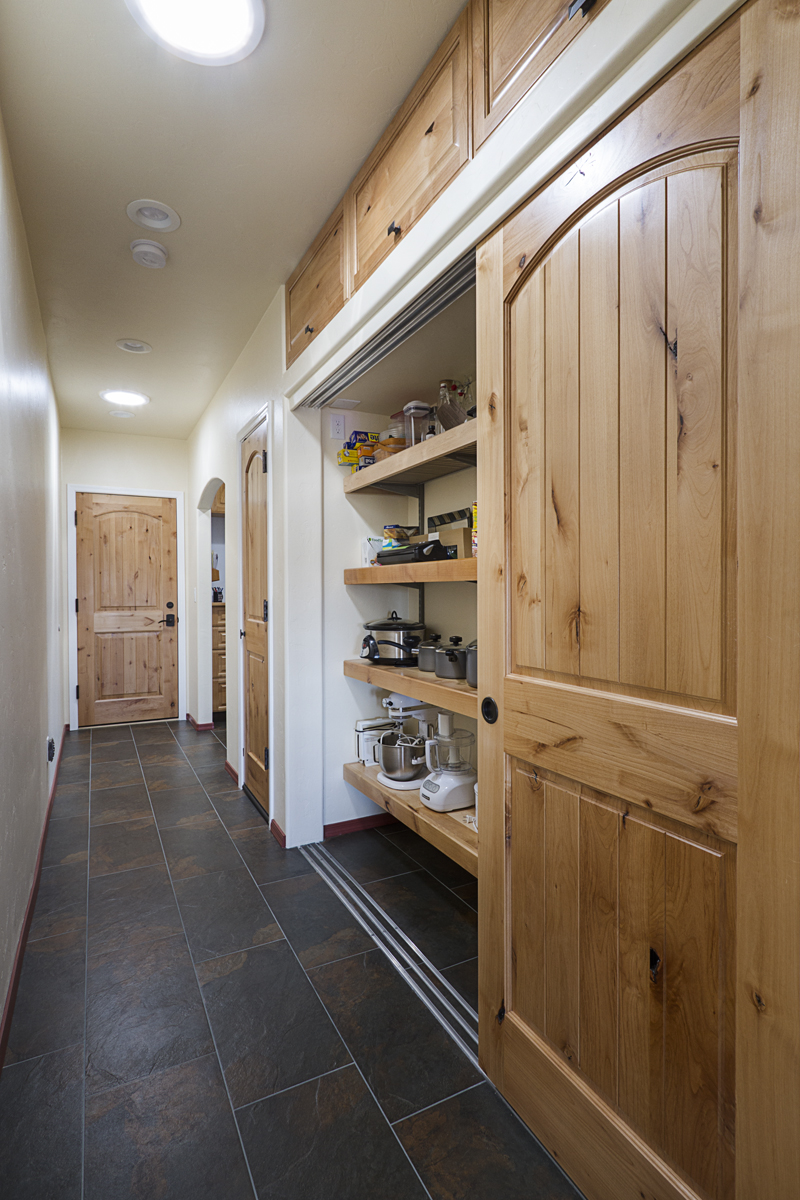 This pantry is concealed behind sliding knotty alder doors. At the end of the hall, the Laundry Room invites you in.