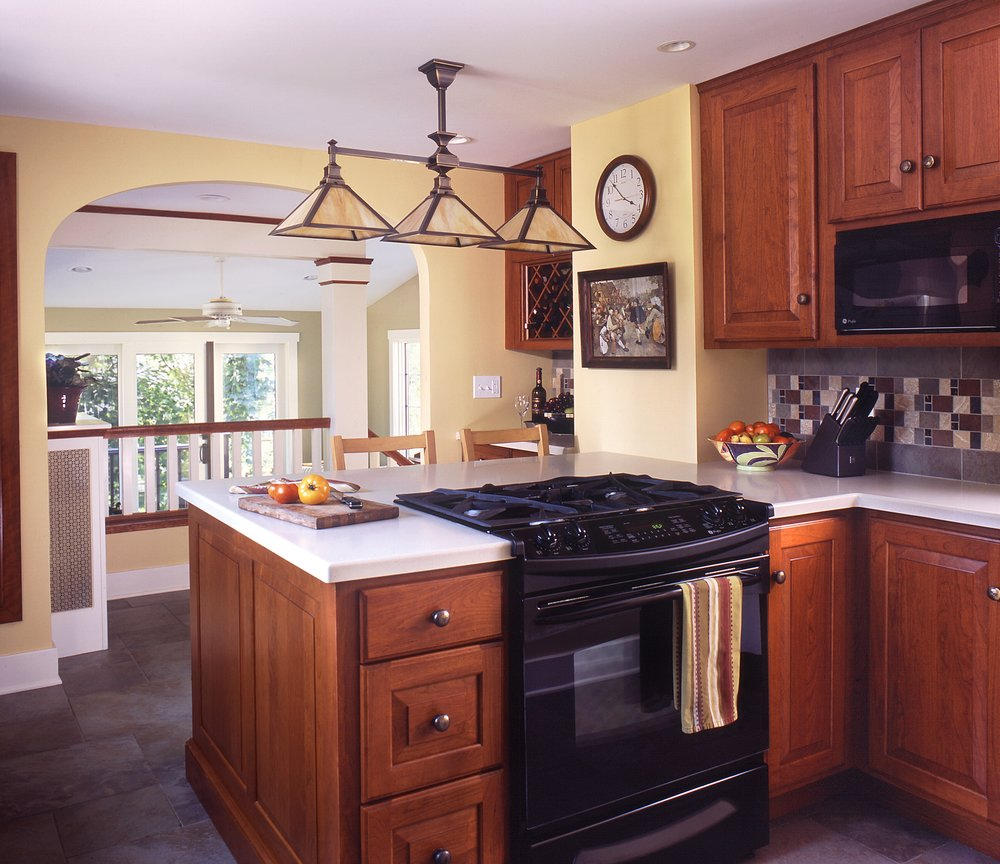 We opened the Kitchen up to the Sun-room beyond, allowing a connection  between the cook and the family. We re-located, re-purposed and added  cabinetry to transform the Kitchen while keeping its craftsman  character.