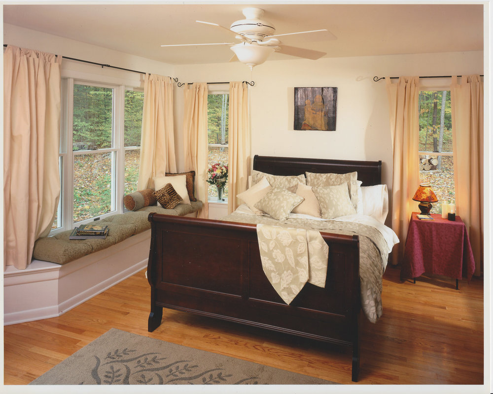 View of Master Bedroom with a built-in window seat that doubles as storage space for the bed linens.