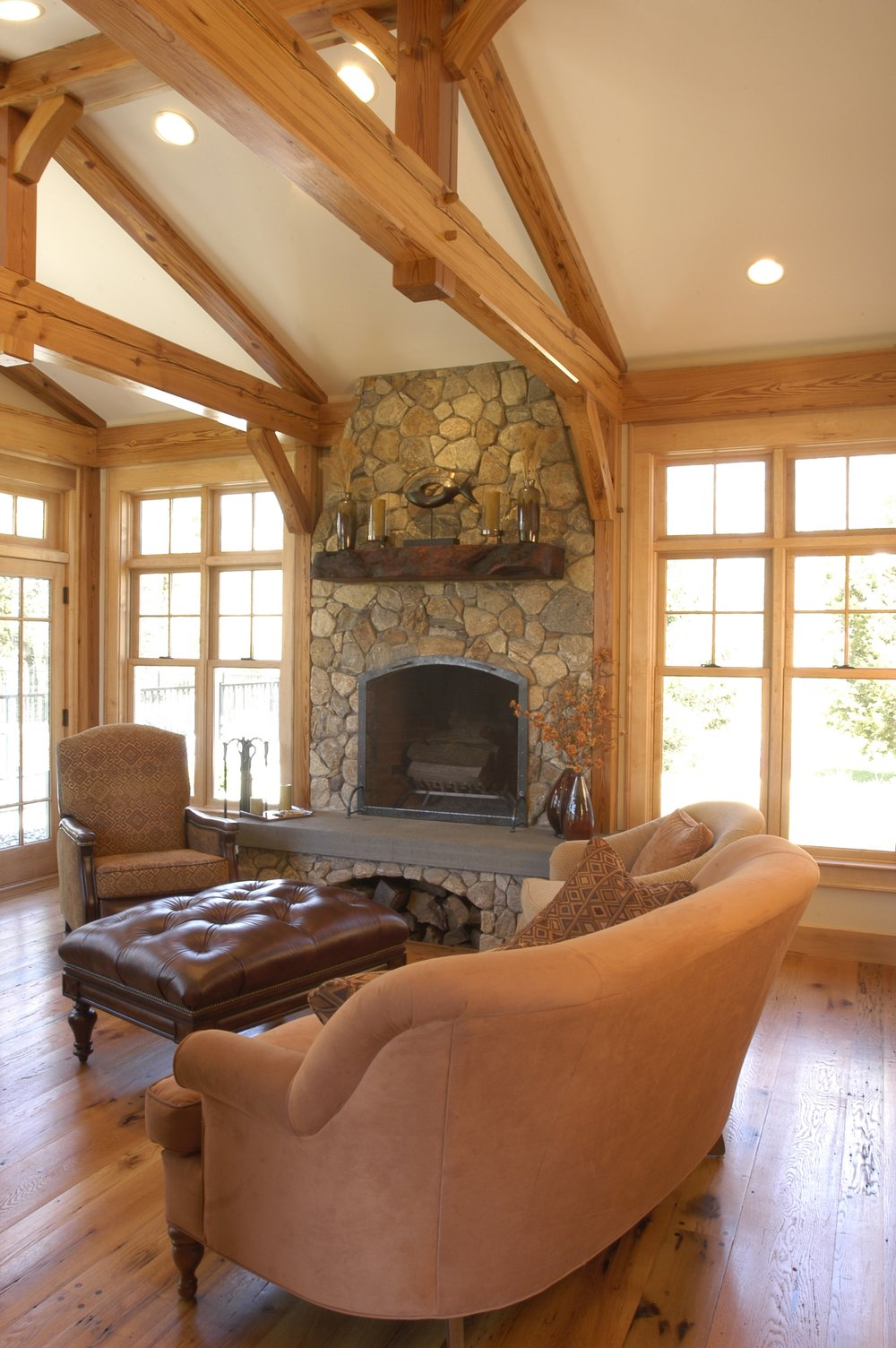The Family Room features heavy timber framing built from recycled  timbers, hand pegged. The tall windows with transoms above flood the  space with light.
