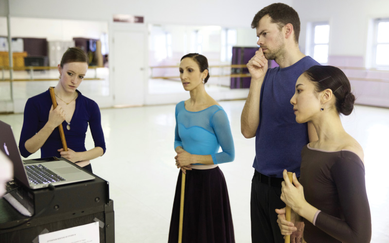 Alberta Ballet Company Artists Jennifer Gibson, Hayna Gutierrez and Luna Sasaki watch a recording of their rehearsal with Associate Artistic Director and Choreographer, Christopher Anderson