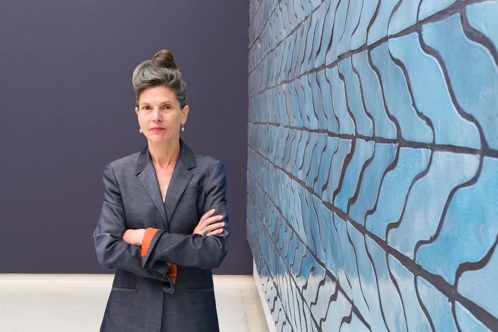 Ingrid Schaffner, curator of the 57th  Carnegie International  in front of Sarah Crowner's  Wall (Wavy Arrow Terracotta) , 2018.   © Carnegie Museum of Art, Pittsburgh. Photo: Bryan Conley.