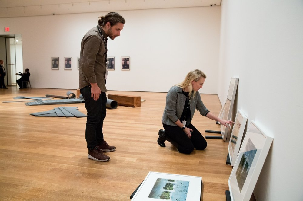 Fisher with Curatorial Assistant Luke Baker at MoMA with works by firm Superstudio for the 2016 exhibition   From The Collection, 1960–1969  . Image by Claudio Papapietro, courtesy The Wall Street Journal.