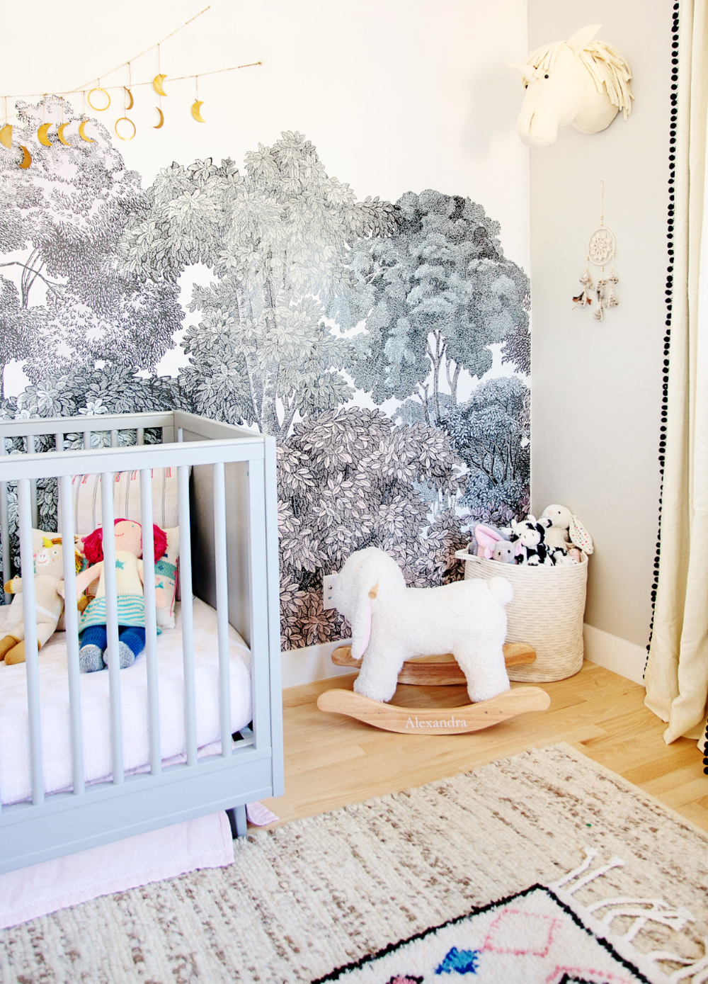 Veneer Designs  creates a whimsical baby girl nursery in true Boho baby style with the woodland wall mural, the layered rugs, moon garland and plenty of storage for toys and stuffies.