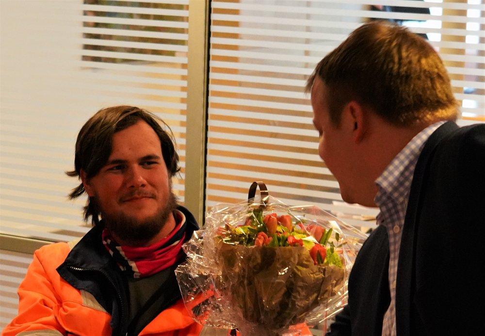 Bildet: Nikolai mottar velfortjente blomster fra stortingsrepresentant Erlend Wiborg (FrP), som er leder for arbeids- og sosialkomiteen på Stortinget.