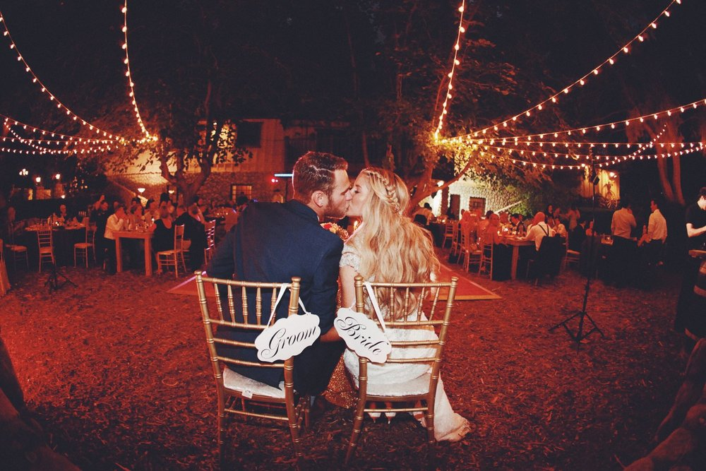 bride and groom kissing at their wedding reception under bistro lighting