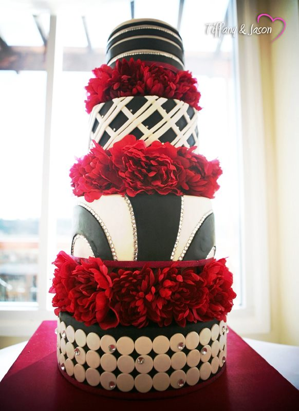 black, white wedding cake with rhinestones and red flowers