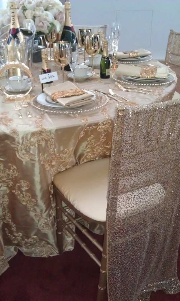 gold wedding table with gold sequin chair covers on chiavari chairs