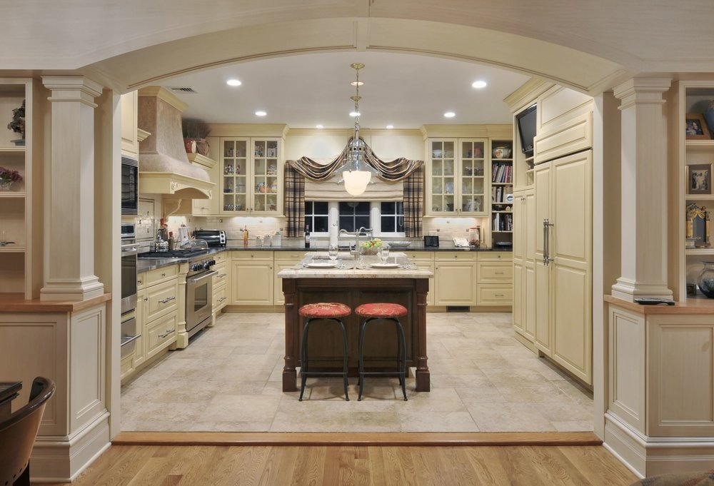 Traditional style kitchen with light yellow colored theme and spacious floor