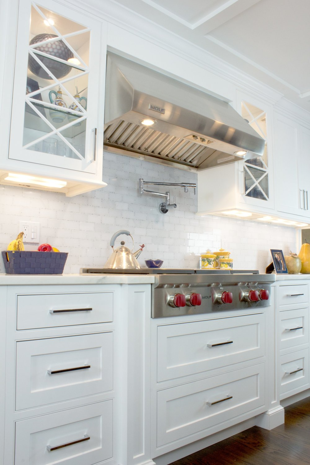 Transitional style kitchen with stainless range and range hood