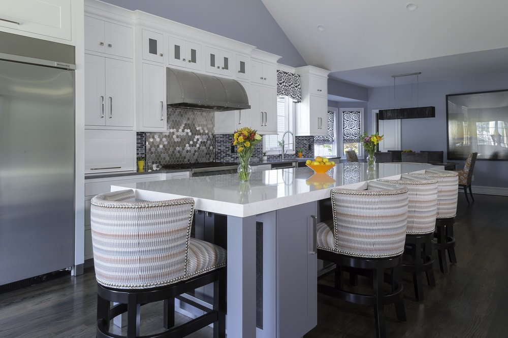 Transitional style kitchen with modern comfy chair at the center island