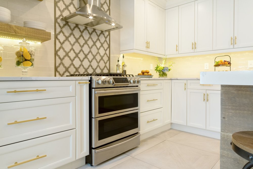 Transitional style kitchen with stainless steel range oven and hood