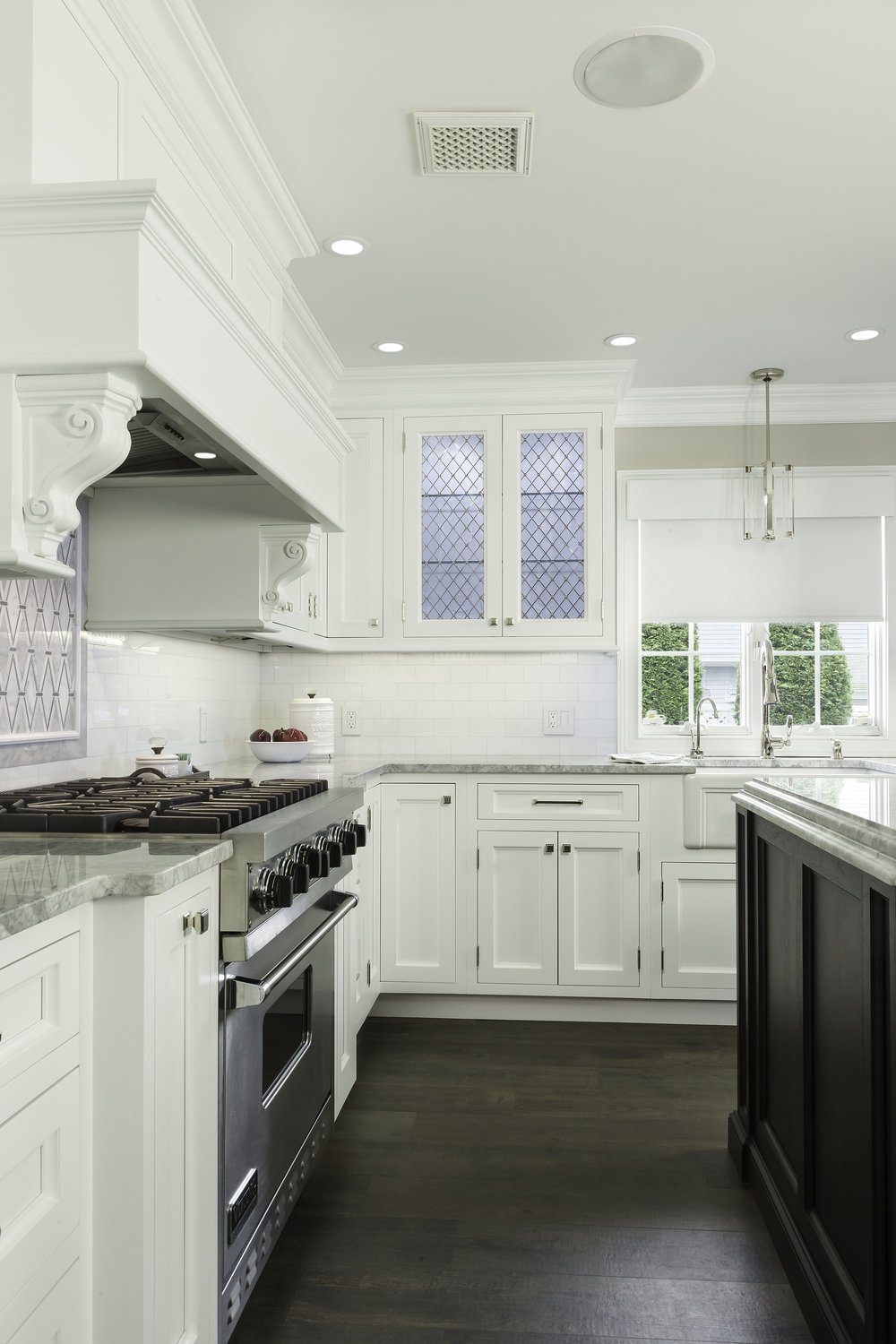 Transitional style kitchen with custom built range hood