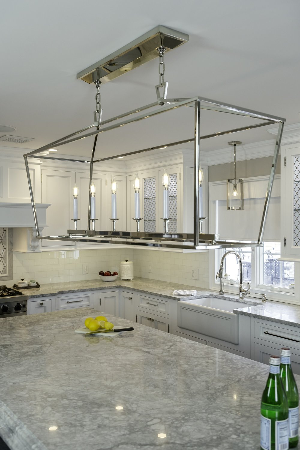 Transitional style kitchen with candle chandelier and marble countertop