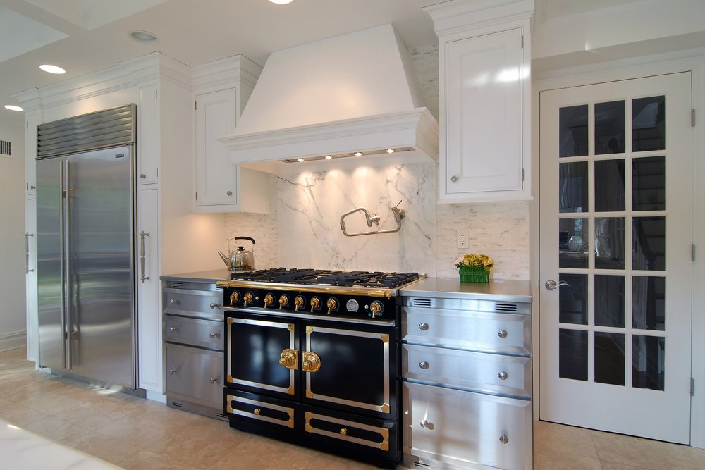 Transitional style kitchen with a range hood and a black range oven