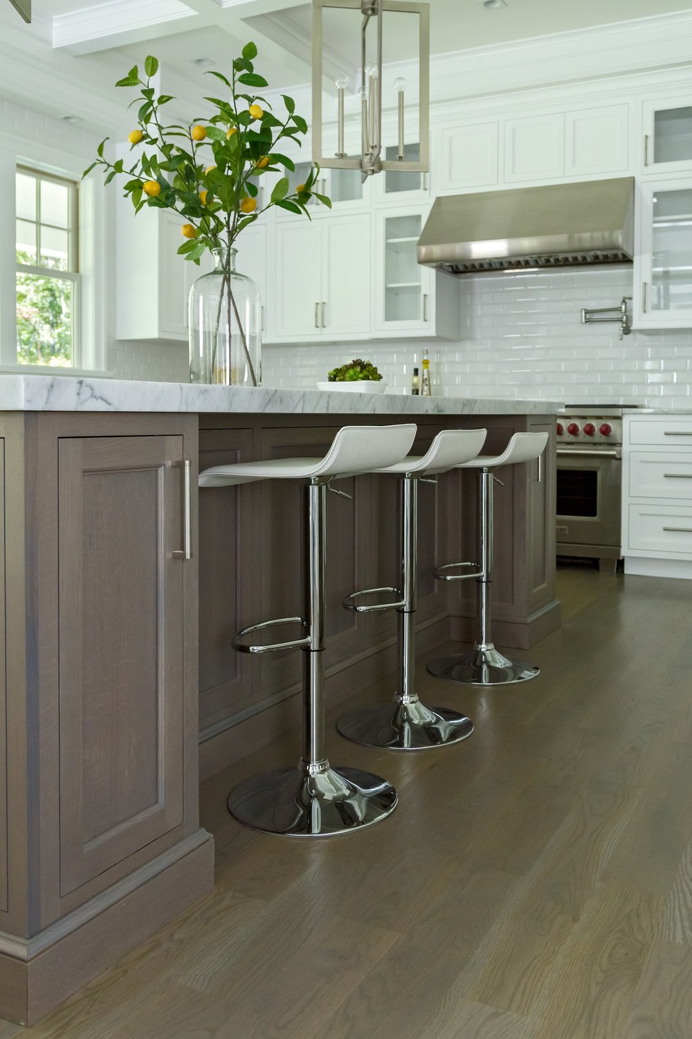 Transitional style kitchen with three counter stools