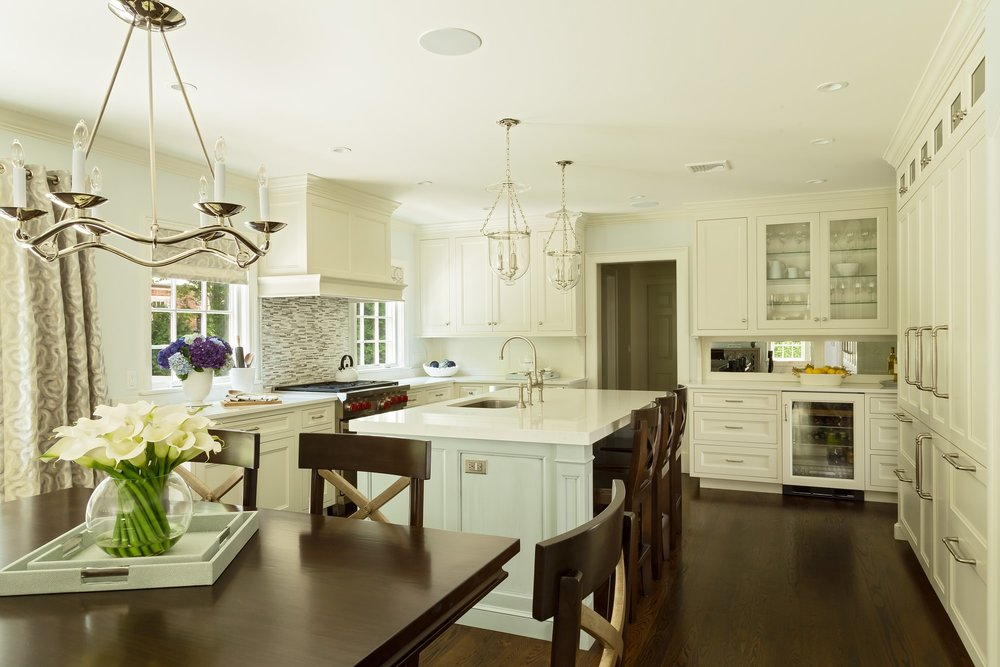 Transitional style kitchen with hanging chandelier on breakfast table