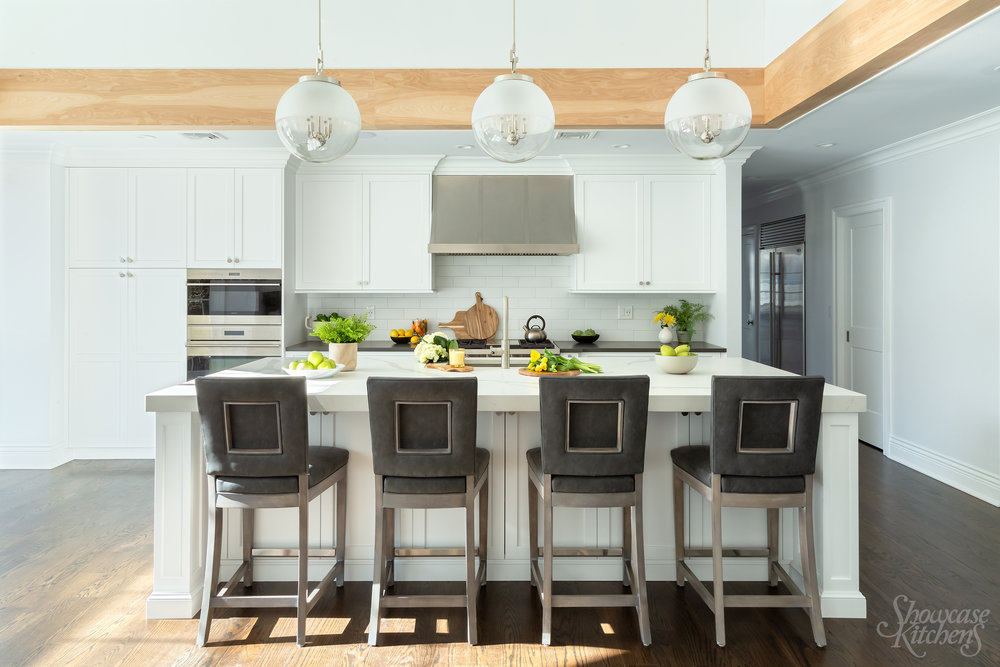 Transitional style kitchen with oak beam and contemporary stools