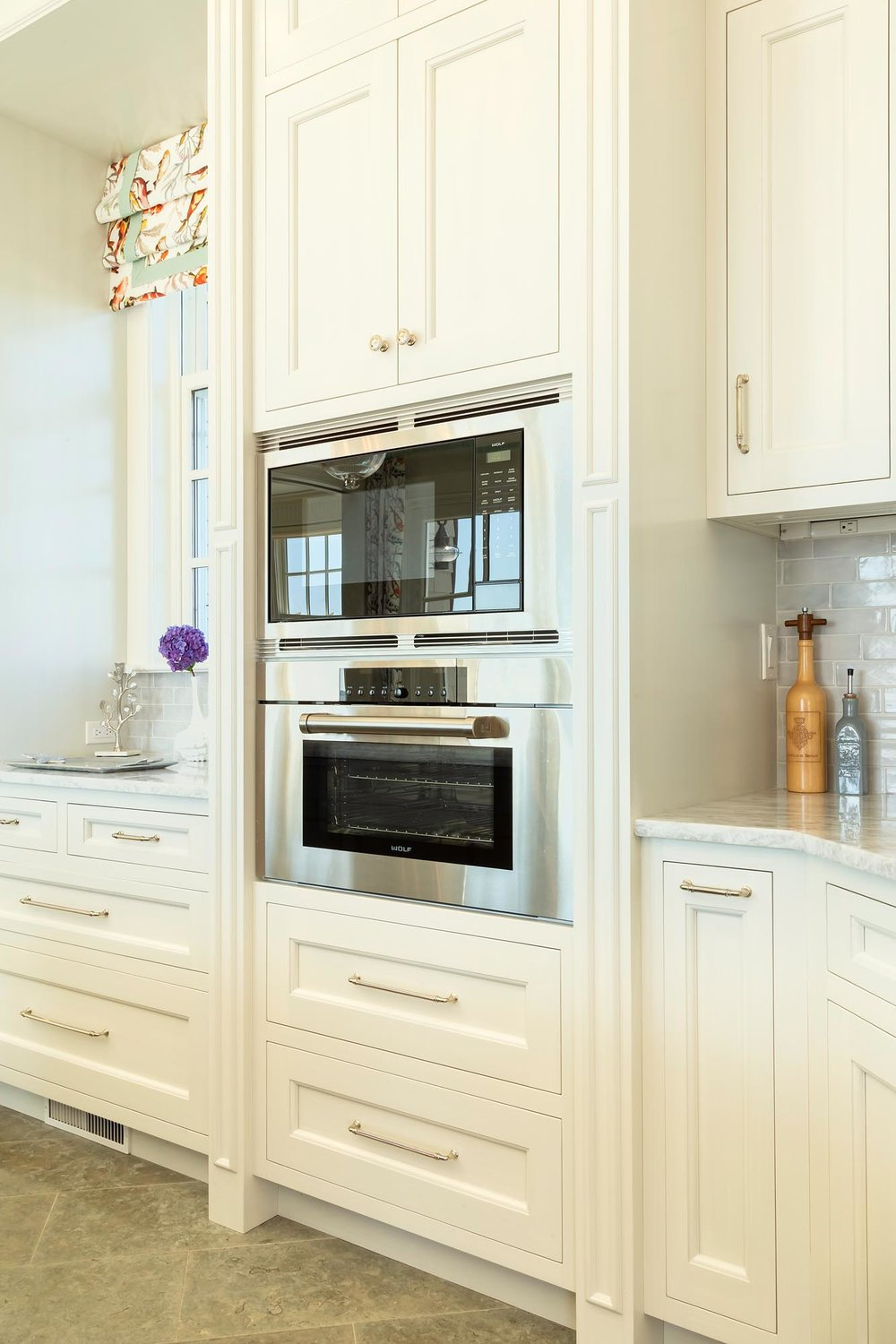 Transitional white kitchen with Wolf microwave and oven