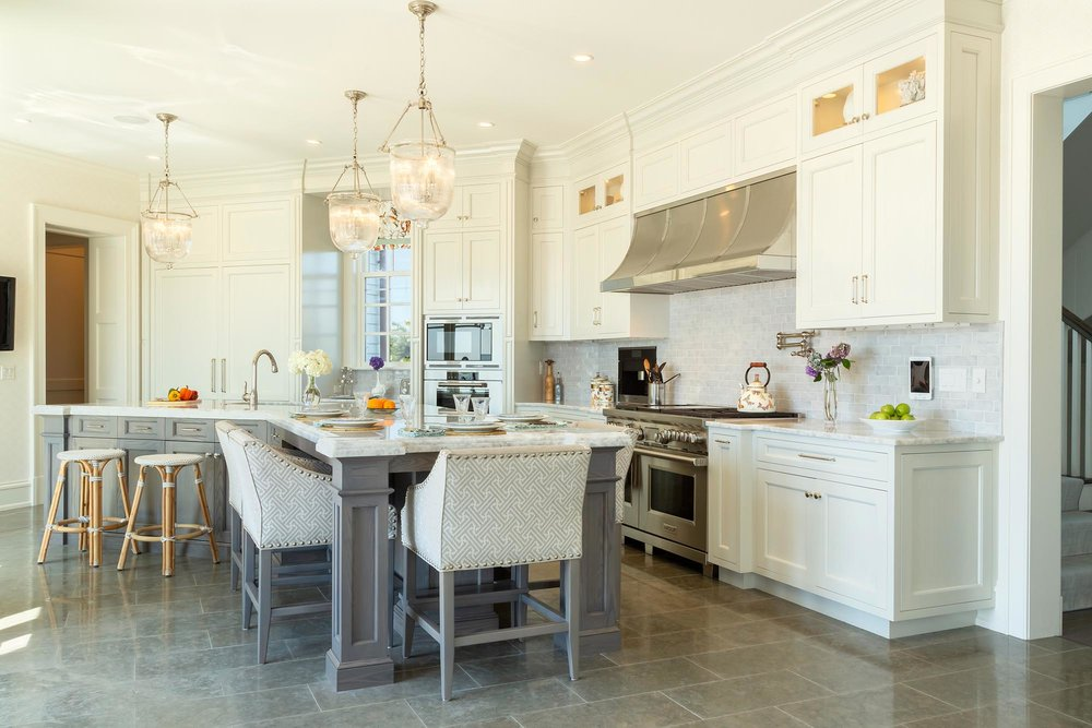 Transitional white kitchen with V-shaped center island and Wolf oven
