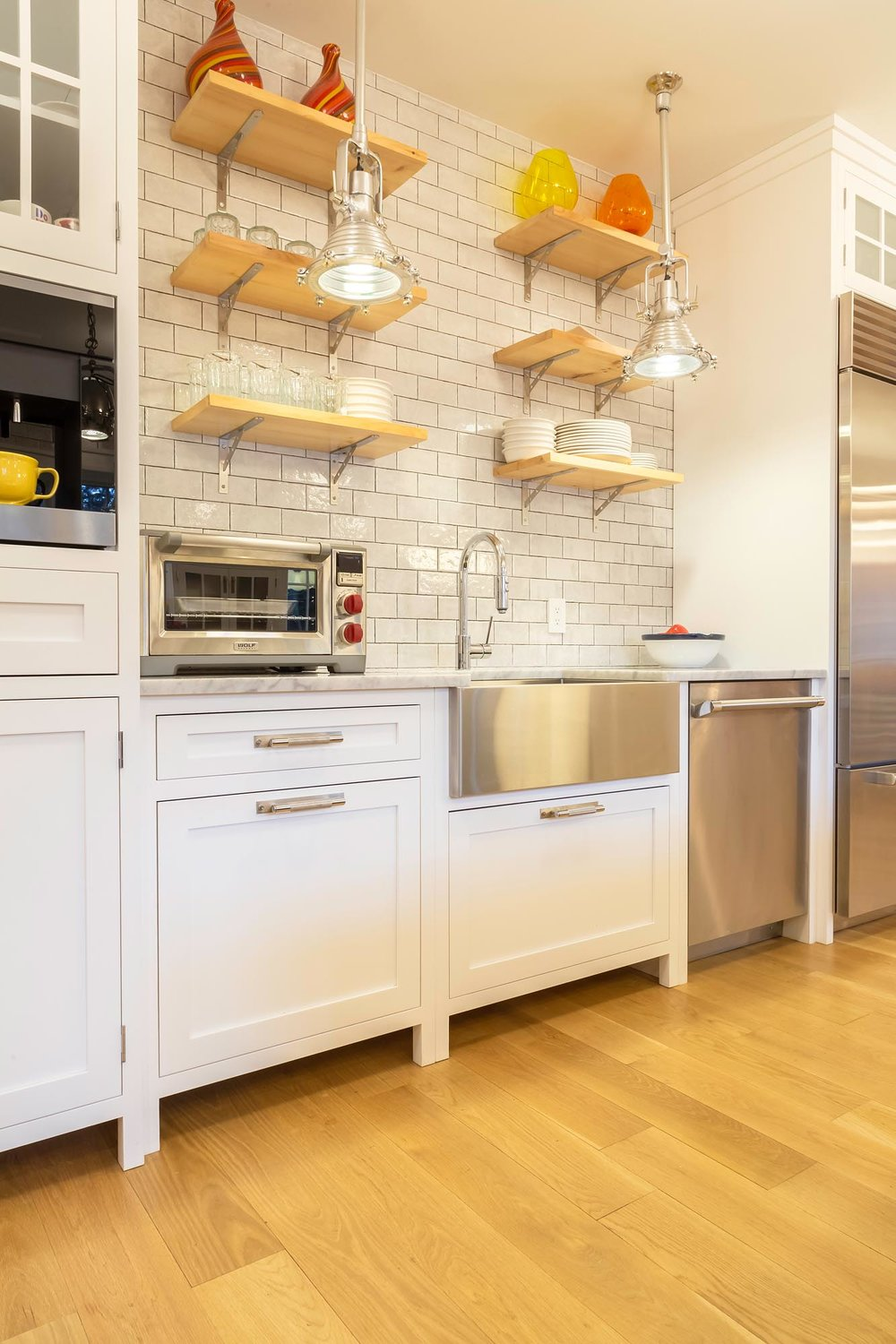 Transitional white kitchen with cabinets and elevated wooden shelves