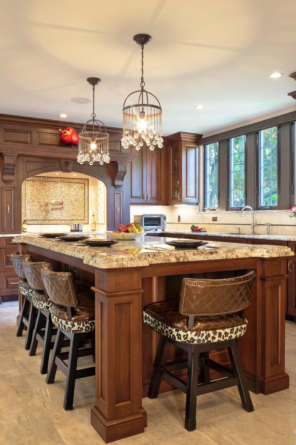 Traditional kitchen with rich dark walnut cabinetry and double height granite countertop