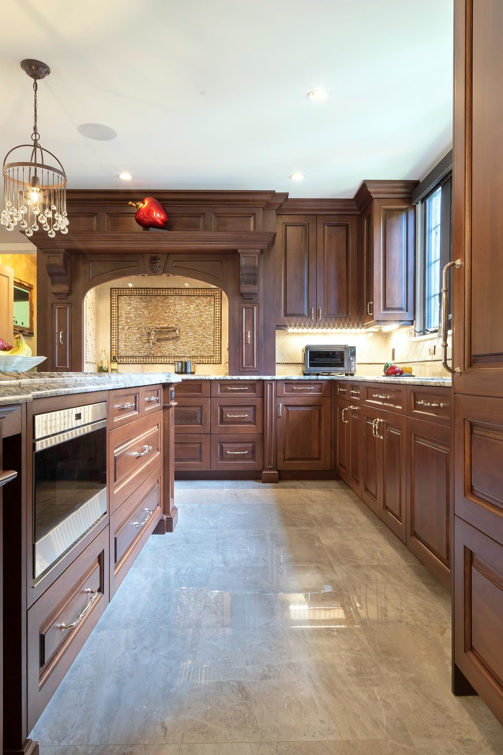 Traditional kitchen with rich dark walnut cabinetry with polished porcelain floor