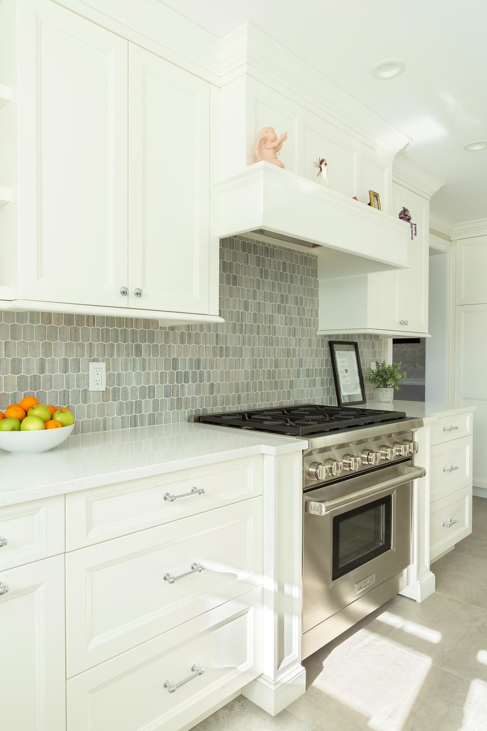 Transitional white kitchen with mantle hood and gray backsplash