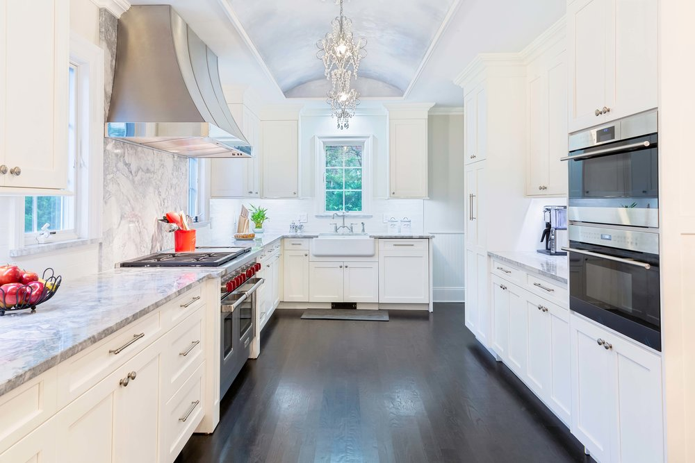 Transitional kitchen with barrel ceiling, farmhouse sink, granite backsplash and ebony stained wood flooring