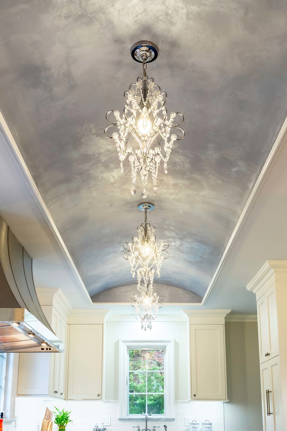 Vaunted ceiling with hanging chandeliers within a bright transitional style kitchen
