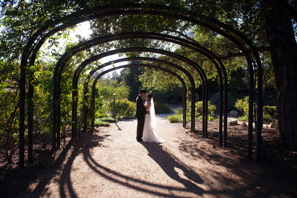 Bride and groom kissing under archway at Descanso Gardens in La Canada Flintridge.
