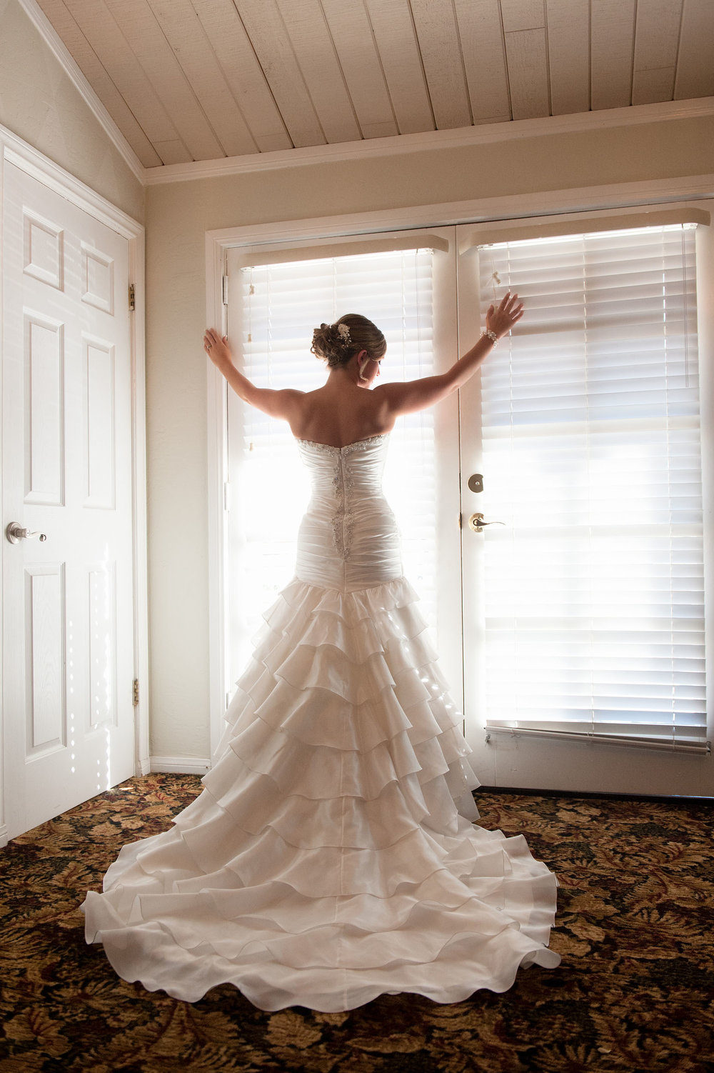 Bride facing window, displaying her wedding dress train at Grand Tradition Estate & Gardens in Fallbrook.