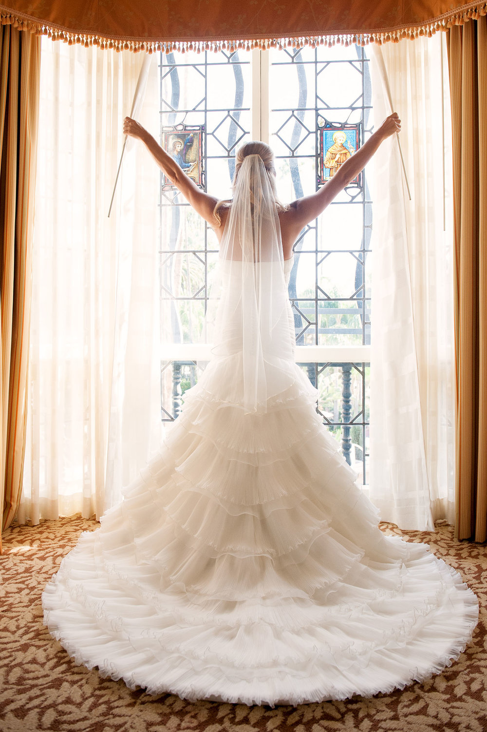Bride shows off wedding dress train at the Mission Inn Hotel & Spa in Riverside.