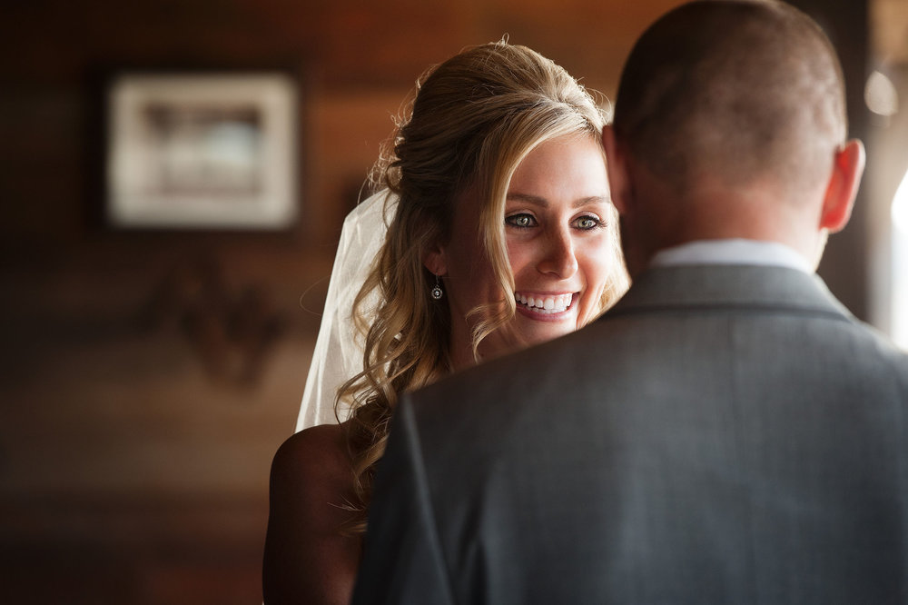 Bride smiles at groom during wedding ceremony at Orange County Mining Co. in Orange.