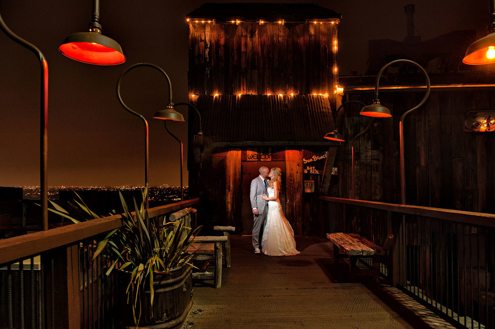 Bride and groom at night at the entrance of the Orange County Mining Co.