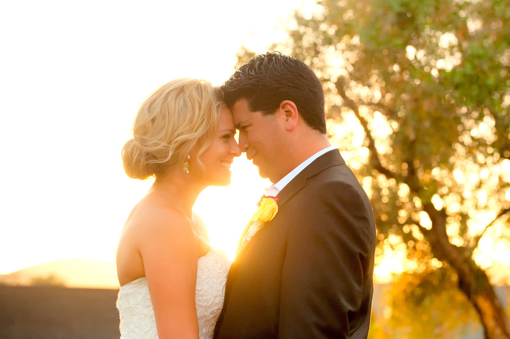 Bride groom forehead to forehead with setting sun shining through from behind in San Juan Capistrano.